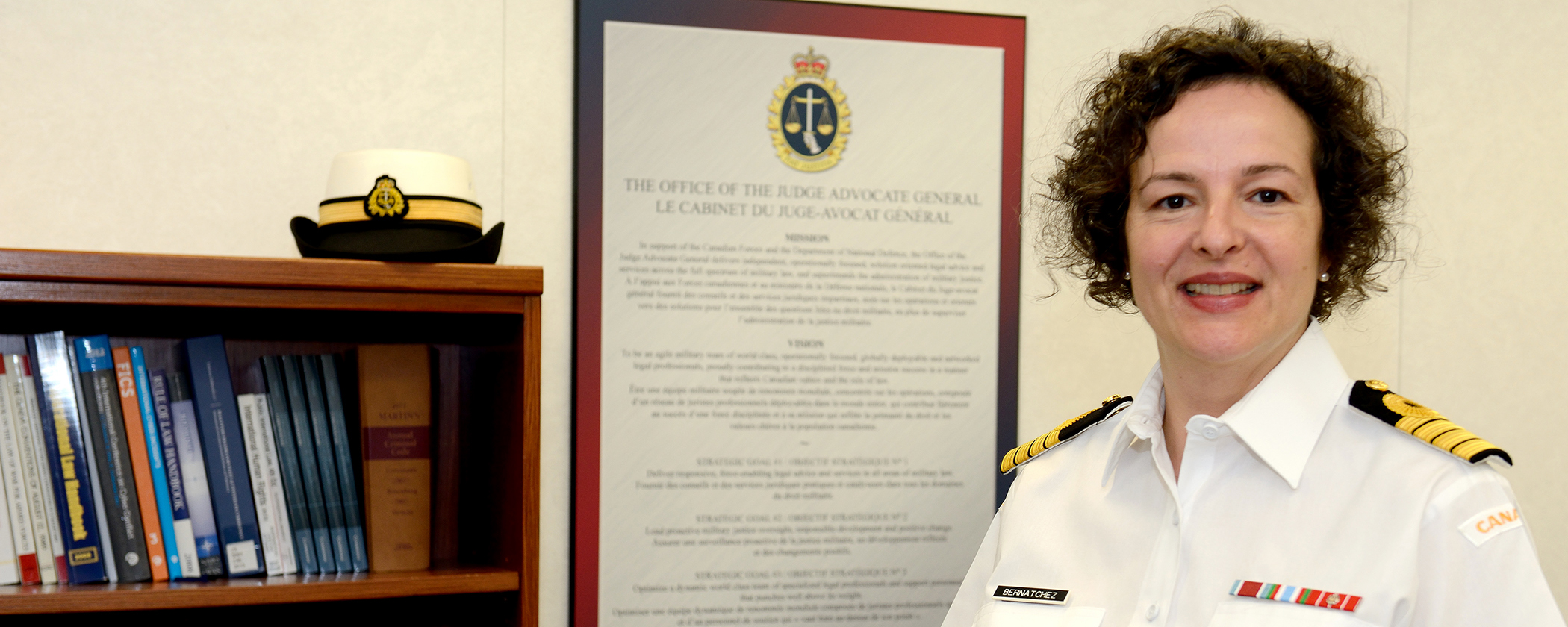 A female Navy officer in a white uniform stands in front of a bookshelf upon which her hat is placed. There is a poster on the wall behind her.