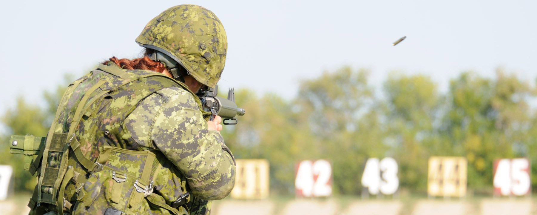 Slide - A female Canadian Army soldier dressed in camouflage combat gear shoots an assault rifle on a shooting range.